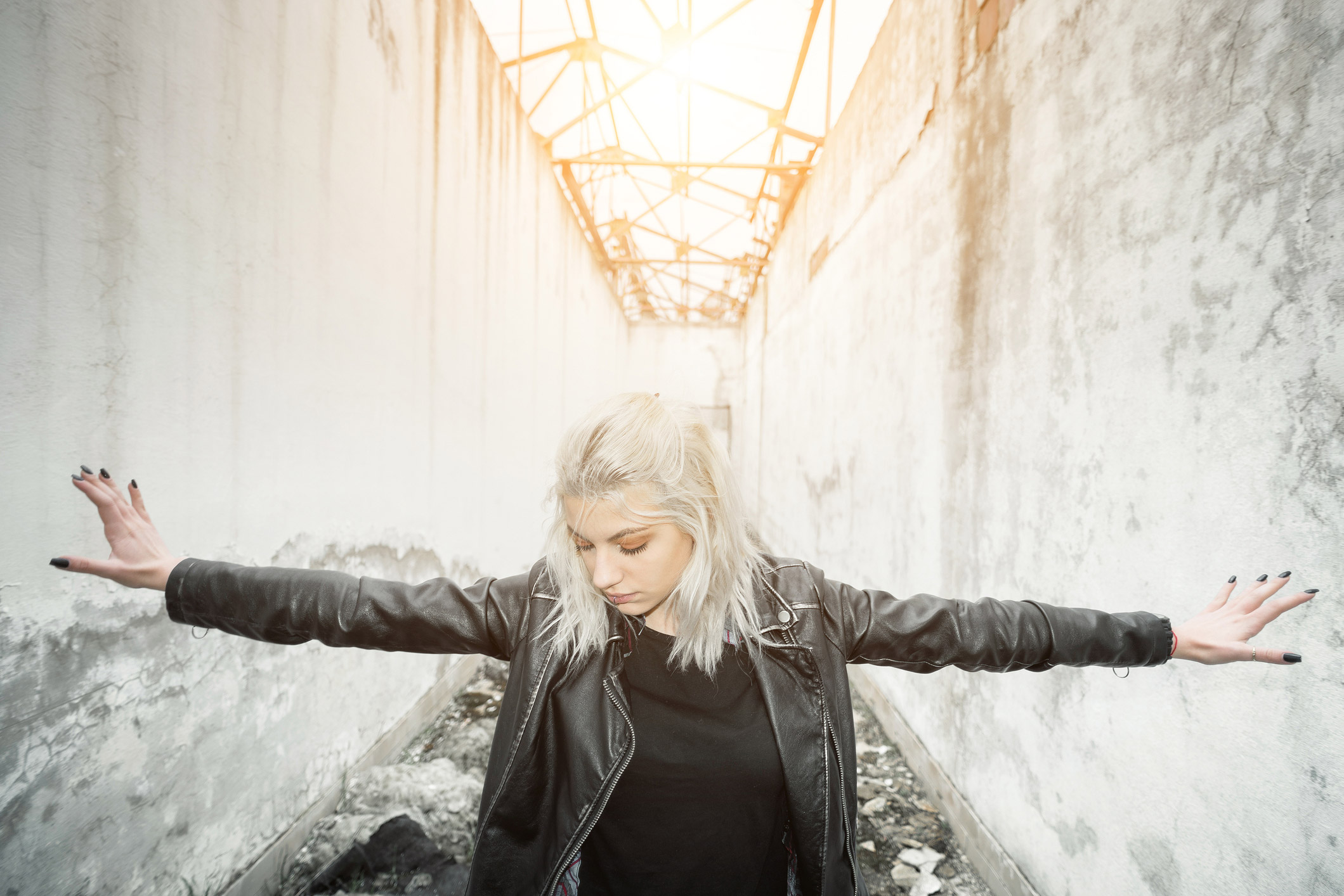 A young, white haired girl in a black leather jacket with black fingernails has her hands out, fingers against white walls on both sides, inside a run down industrial building.
