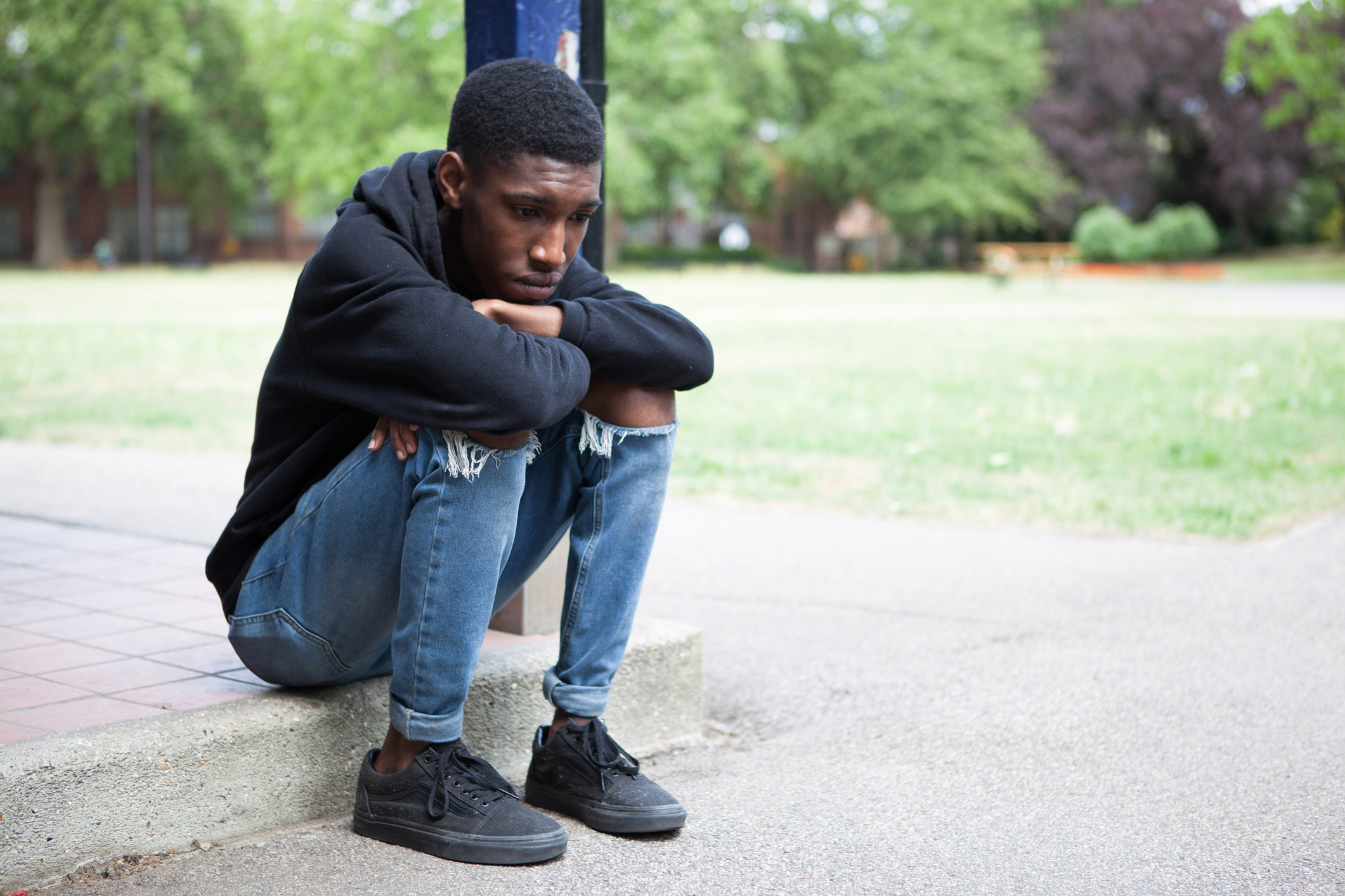 A young African American man sits on a sidewalk of a building at a curb pondering somewhat worried.