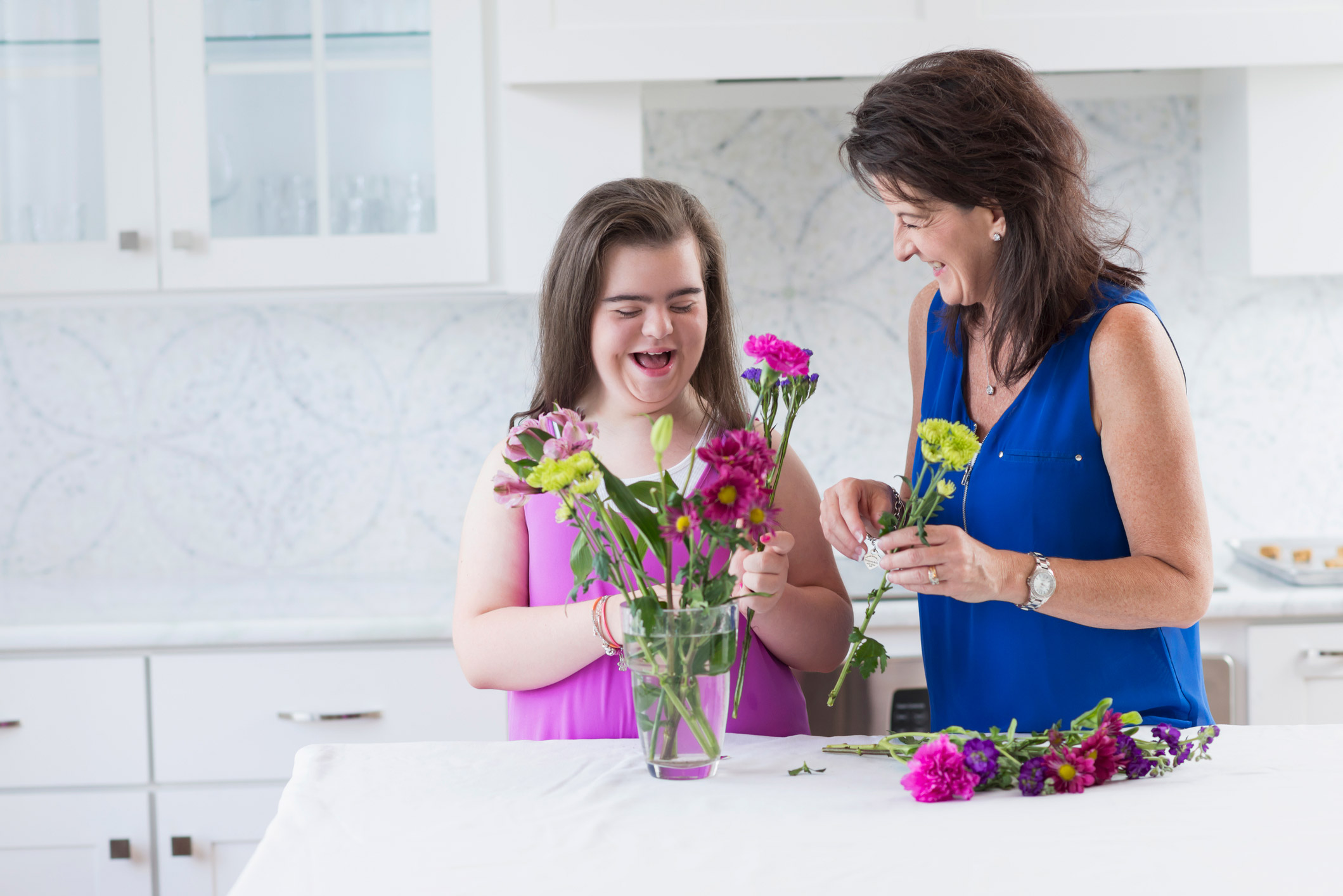 A mother is laughing with her daughter, and looking at her as her daughter looks down. They are both placing flowers in a clear glass vase on a white table in the kitchen. All the cabinets and drawers are white.
