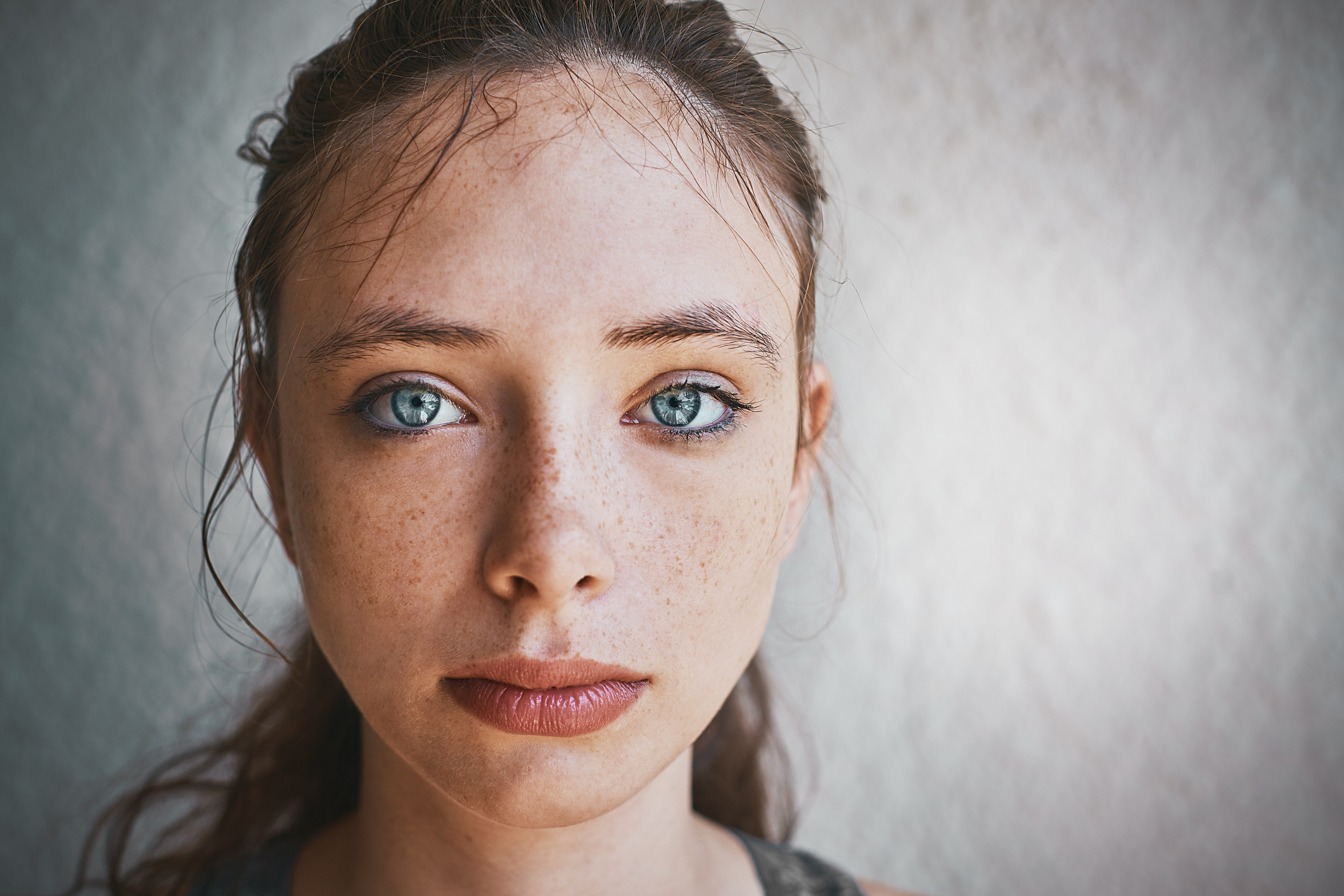 A young girl with freckles and grayish blue eyes with her hair pulled back stairs into the camera. There is a gray background.